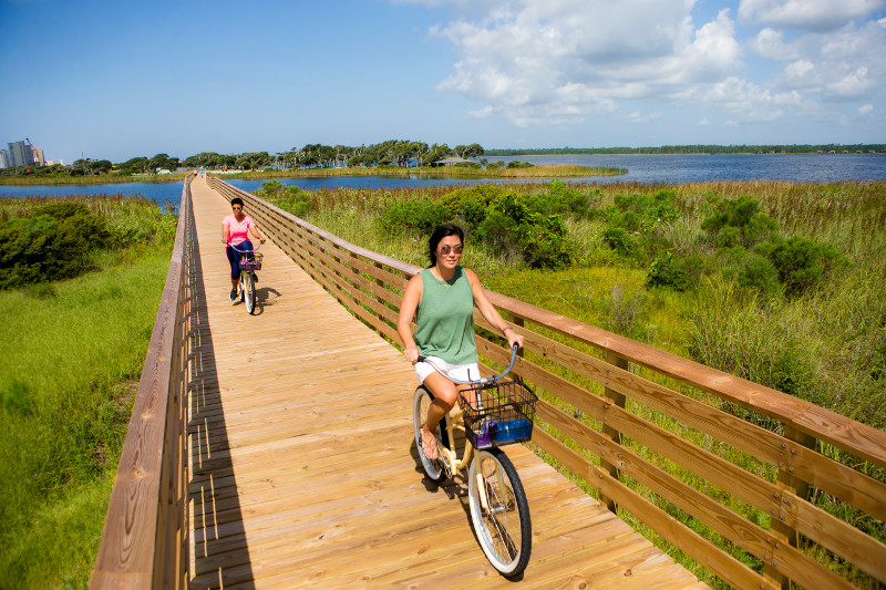 Women biking on Hugh S Branyon Backcountry Trail in Gulf Shores, AL