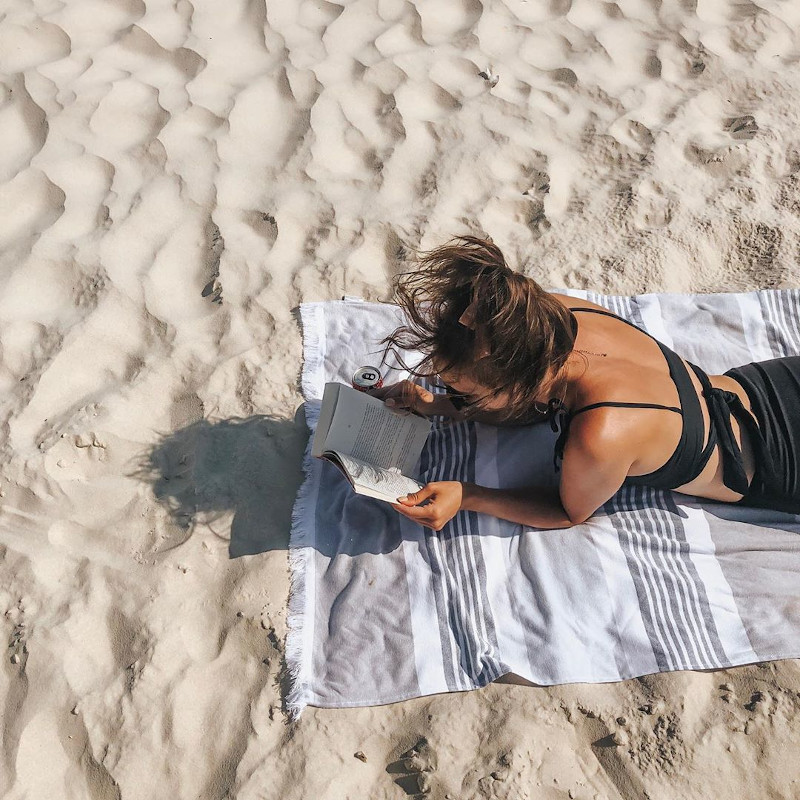 Girl reading on the beach in Gulf Shores, AL