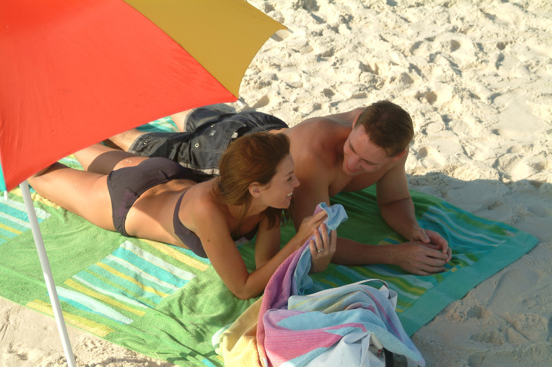 young couple on beach towel under umbrella