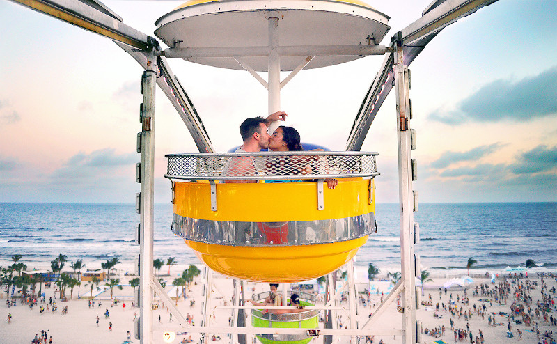 Couple kissing on ferris wheel at the beach