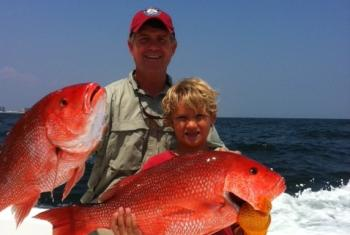 Father and son holding red snapper