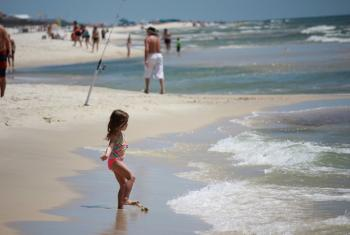 young girl plays in ocean at Gulf Shores
