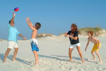 Famiy playing football on Alabama's beaches