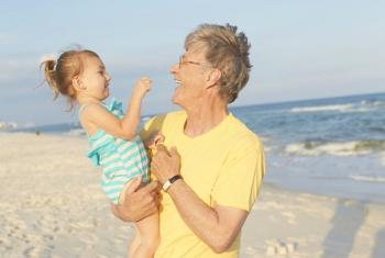 Man holding baby on Gulf Shores Al beach