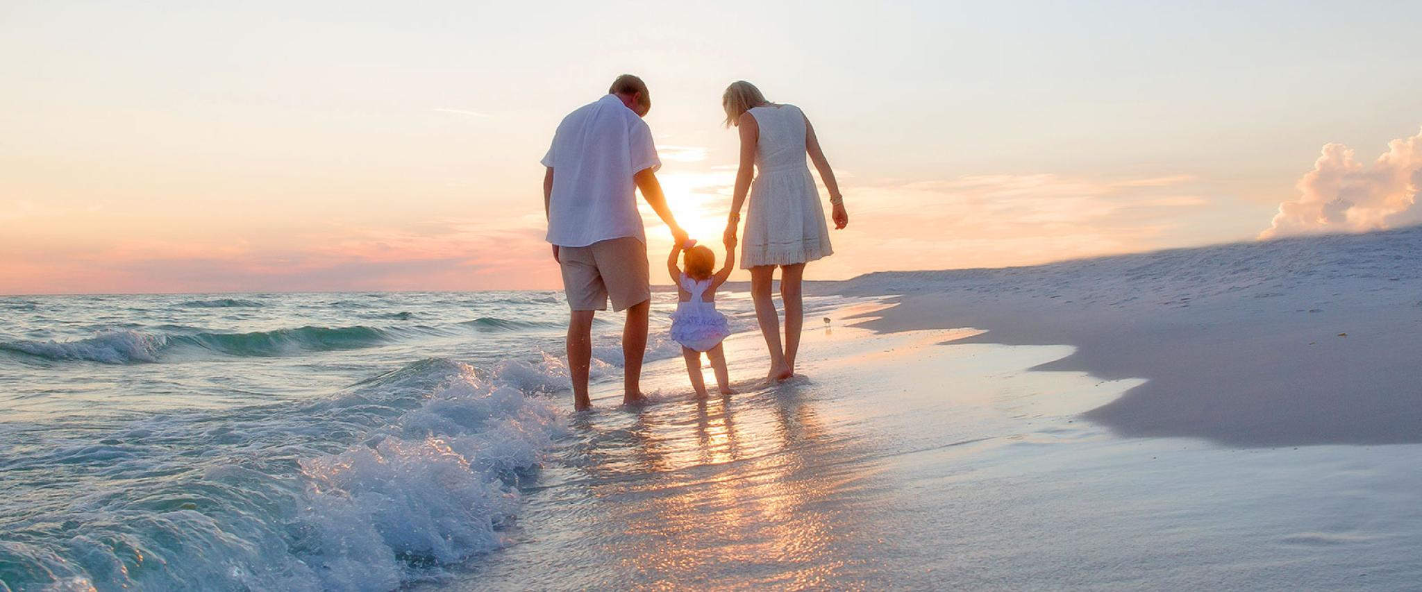 Young Family walks along Alabama's white sand beaches at sunset
