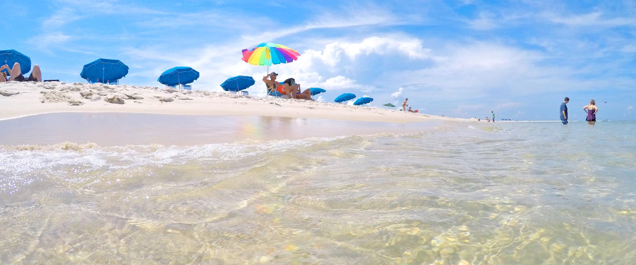 Clear surf and umbrellas along Alabama's White Sand Beaches