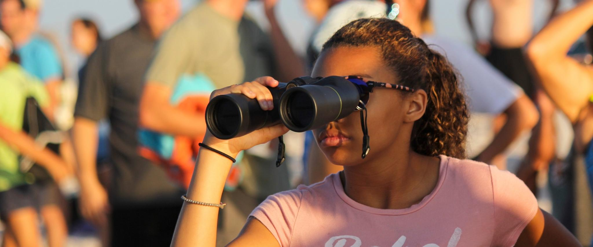 girl with binoculars at foley sport event
