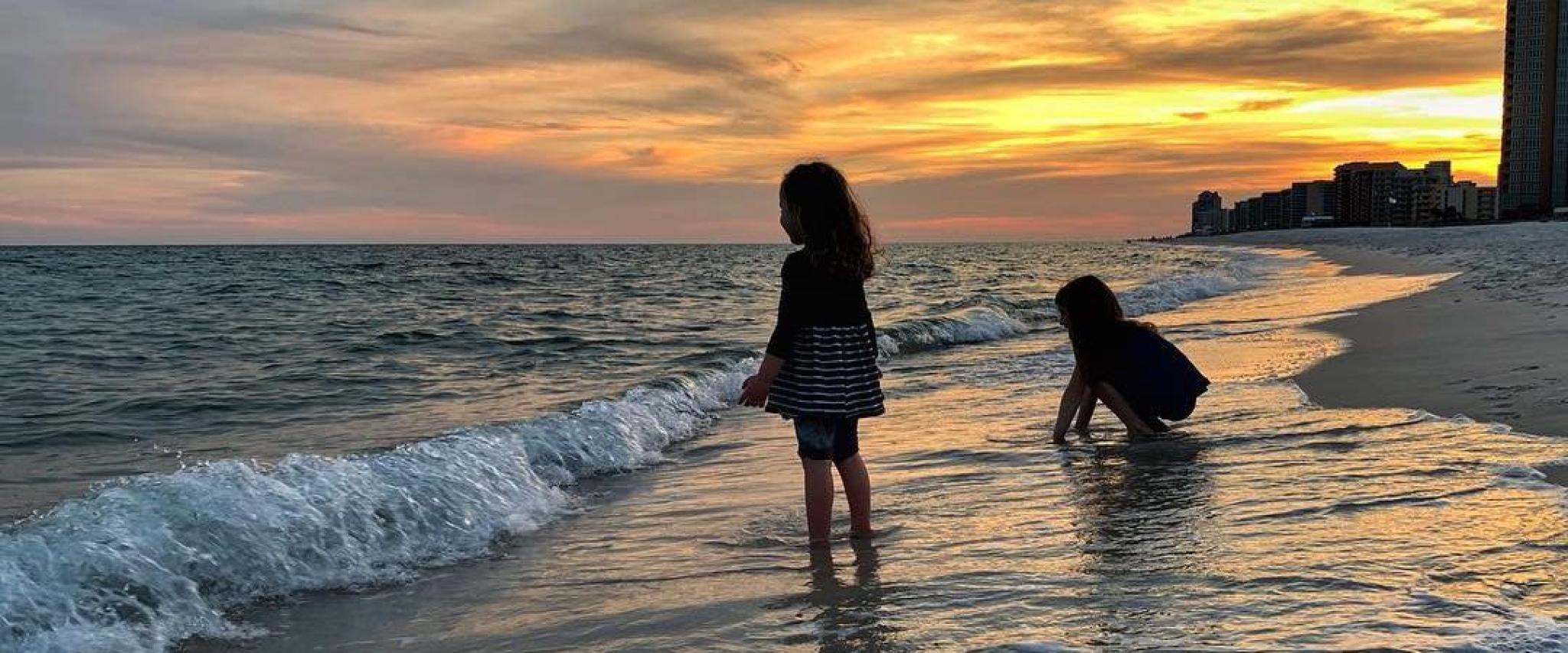 Sisters playing on the beach at sunset Orange Beach, AL