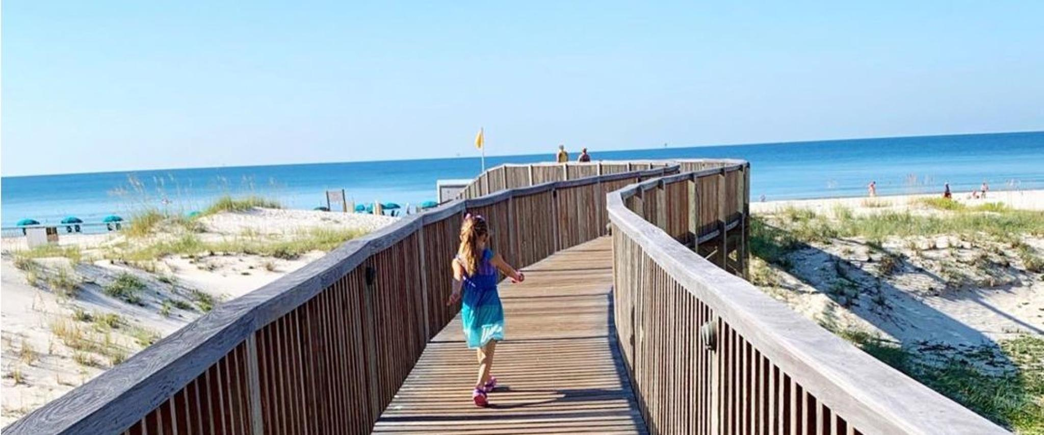 Little girl running out to the beach in Gulf Shores, AL