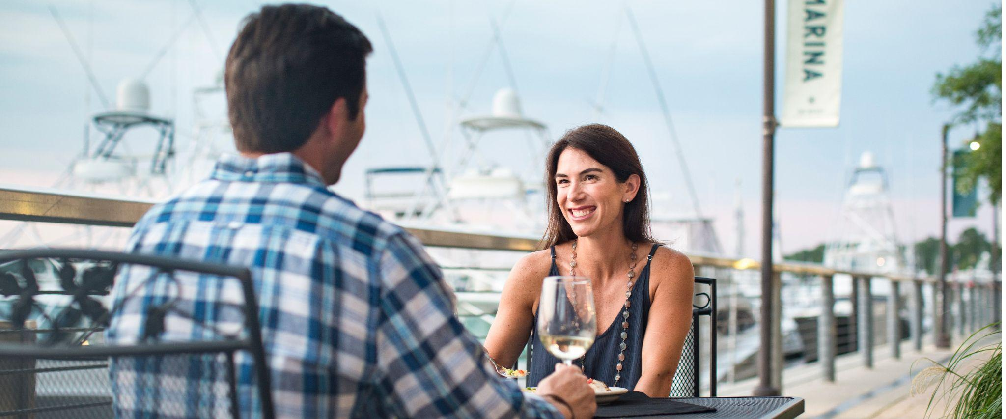 couple drink wine at The Wharf Orange Beach AL